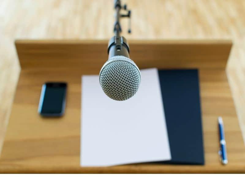 speaking at podium, bearing testimony